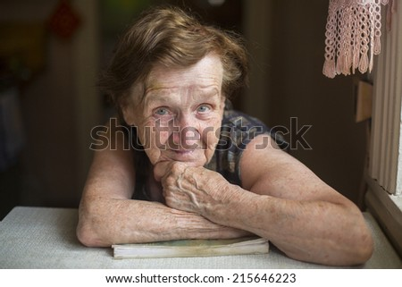 Portrait of an elderly woman with expressive look in her house. - stock photo