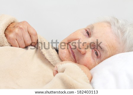 Portrait of an elderly wrinkled woman lying in the bed - stock photo