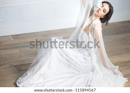 Portrait of an elegant bride sitting and holding her veil up to her face. - stock photo