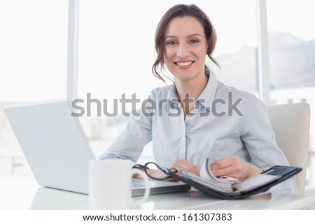 Portrait of an elegant businesswoman with laptop and diary in a bright office - stock photo