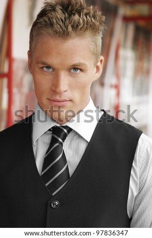 Portrait of an elegant good looking young businessman outdoors - stock photo