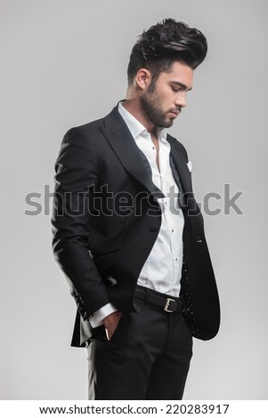 Portrait of an elegant young man in tuxedo holding his hands in pocket while looking down - stock photo