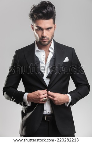 Portrait of an elegant young man looking at the camera while closing his tuxedo. On grey background. - stock photo