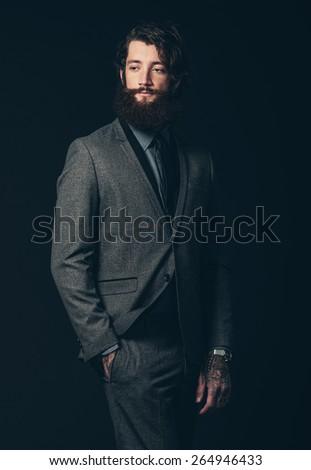 Portrait of an Elegant Young Man with Facial Hair, Wearing Formal Suit with Hand on his Pocket, Looking to the Left of the Frame Seriously. Isolated on Black Background. - stock photo