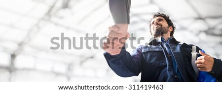 Portrait of an engineer giving an handshake, Large copy-space - stock photo