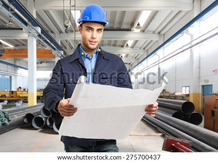 Portrait of an engineer in a factory - stock photo