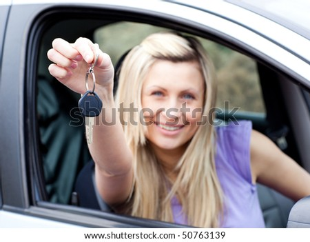 Portrait of an enthusiastic young driver holding a key after buying a new car - stock photo