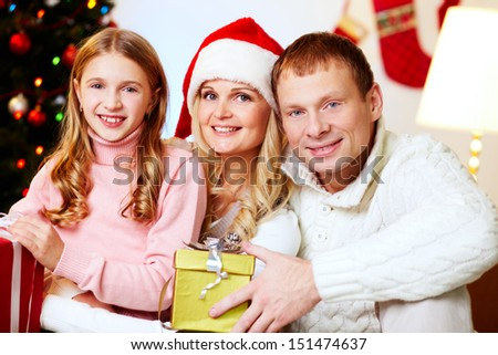 Portrait of an excited family holding Christmas presents - stock photo