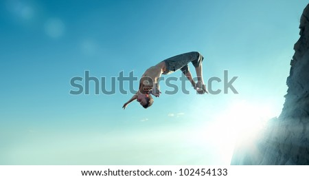 Portrait of an excited young man jumping in air against blue sky - stock photo