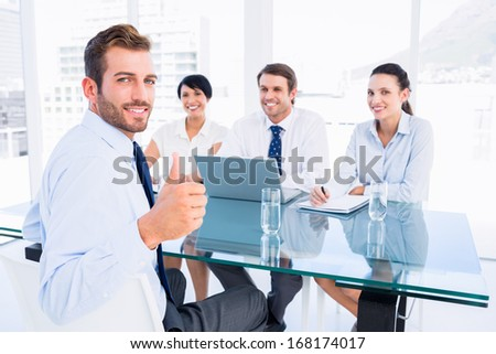 Portrait of an executive gesturing thumbs up with recruiters during a job interview at office - stock photo