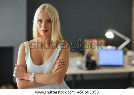 Portrait of an executive professional mature businesswoman sitting on office - stock photo
