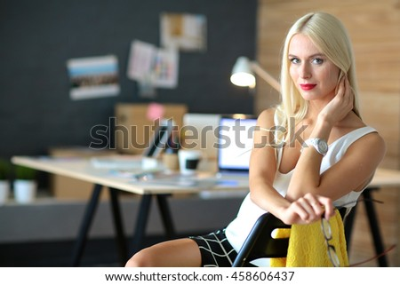 Portrait of an executive professional mature businesswoman sitting on office desk - stock photo