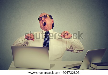 Portrait of an exhausted middle aged business man yawning at work in office sitting at his desk table with many laptop computers. Lack of sleep productivity concept. Sleep deprivation long work hours - stock photo