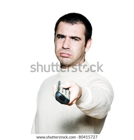 Portrait of an expressive bored man holding remote control in studio on white isolated background - stock photo