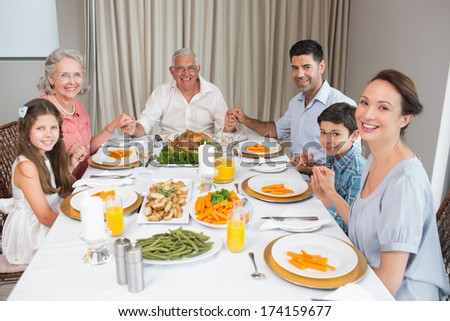Portrait of an extended family at dining table in the house - stock photo