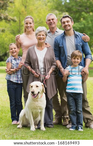 Portrait of an extended family with their pet dog standing at the park - stock photo