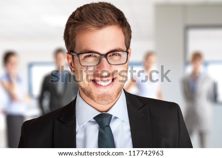 Portrait of an handsome businessman in front of his team - stock photo