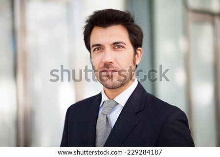 Portrait of an handsome businessman walking outdoors - stock photo