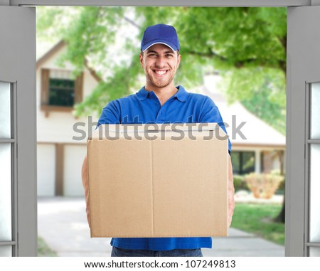 Portrait of an handsome deliverer holding a box - stock photo