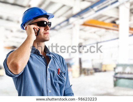 Portrait of an handsome engineer using a mobile phone - stock photo