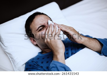 Portrait of an ill man blowing his nose in the bed - stock photo