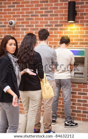 Portrait of an impatient woman queuing at an ATM - stock photo