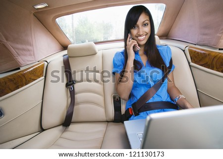 Portrait of an Indian business woman using laptop while communicating on cell phone in car - stock photo