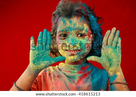 Portrait of an Indian girl with face smeared with colored powder in a red background. Concept for Indian festival Holi. - stock photo