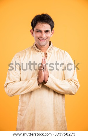 portrait of an Indian man standing in a prayer position, isolated over yellow background. Indian man in welcoming gesture, indian man in namaskar pose, indian male model and ethnic wear - stock photo
