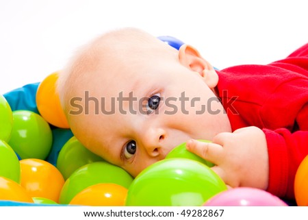 Portrait of an infant lying in colorful balls - stock photo