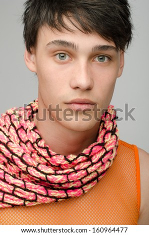 Portrait of an innocent handsome man posing fashion with colored scarf. Young guy with cool messy hairstyle. - stock photo