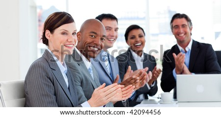Portrait of an international business team clapping in a meeting - stock photo