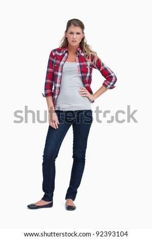 Portrait of an irritated woman standing up against a white background - stock photo