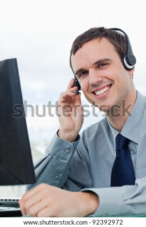Portrait of an office worker using a headset in his office - stock photo