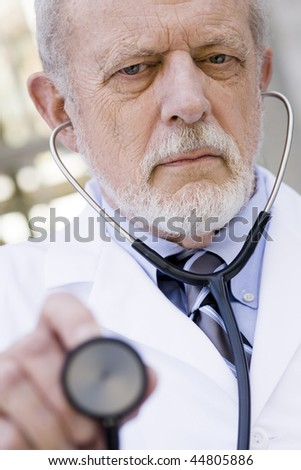 Portrait of an Old Male Doctor with a Stethoscope Pointing to the Camera - stock photo