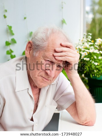 portrait of an old man, he has a headache, his hand on his forehead - stock photo