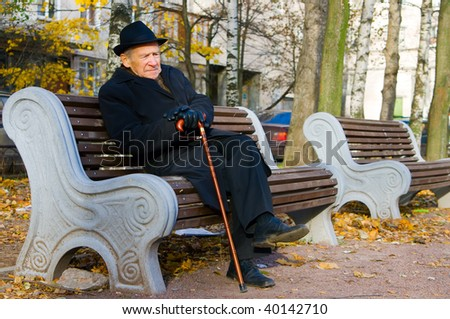 portrait of an old man in a hat sitting on a bench - stock photo