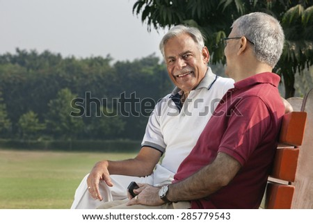 Portrait of an old man in a park - stock photo