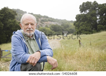 Portrait of an Old Man Resting on a Hiking Trail - stock photo