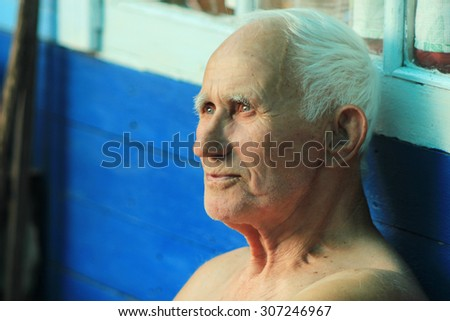 portrait of an old man with a gray head with the wisdom of looking into the distance - stock photo