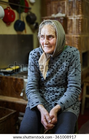 Portrait of an old rural woman indoor with selective focus - stock photo