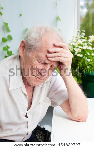 portrait of an old senior man, he has a headache, his hand on his forehead - stock photo