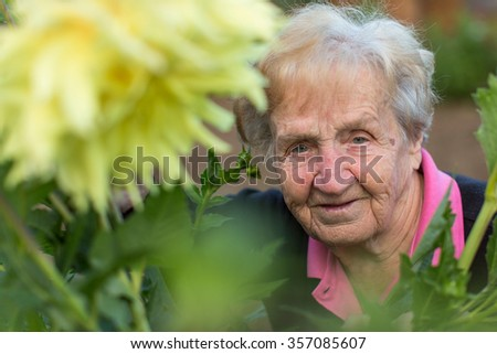 Portrait of an old woman in the garden. - stock photo