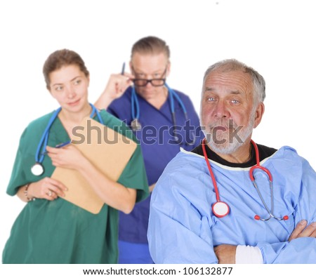 Portrait of an older doctor with arms folded looking smug, standing in front of his team smiling - stock photo