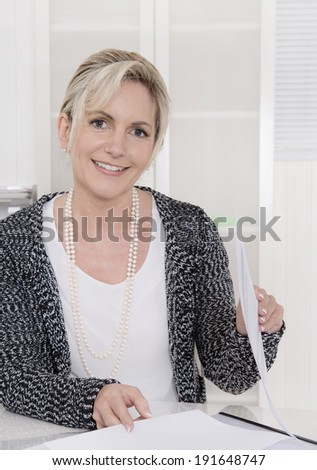 Portrait of an older pretty business woman sitting in the office. - stock photo