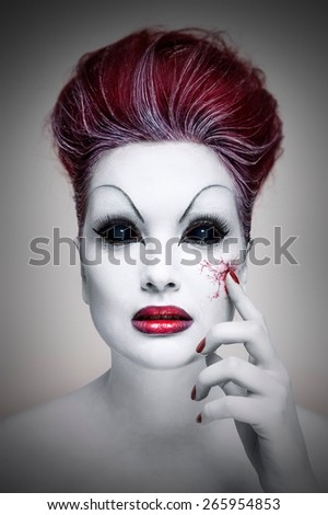 Portrait of an undead girl with red hair, white skin, red lips, black eyes, who is touching herself and it makes her blood vessels visible.  - stock photo