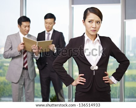 portrait of an unhappy young asian businesswoman with her colleagues talking in the background. - stock photo