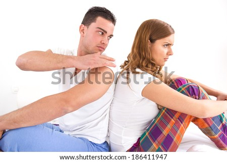 Portrait of an upset young couple sitting separately from each other on the bed in domestic bedroom atmosphere - stock photo