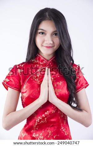 Portrait of an young asian woman making asian greetings, wearing cheongsam isolated on white background - stock photo
