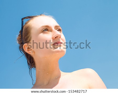 Portrait of an young beautiful woman sunbathing against blue sky - stock photo